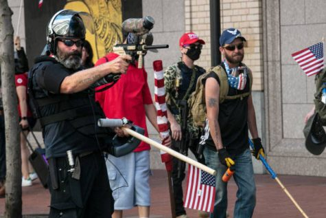 PORTLAND, OR - AUGUST 15 : The Proud Boys, an alt-right group, faces off against Black Lives Matters protesters using mace and a paint ball gun on August 15, 2020 in downtown Portland, Oregon. Demonstrations have occurred on almost a nightly basis in Portland since the killing of George Floyd. (Photo by Paula Bronstein/Getty Images )