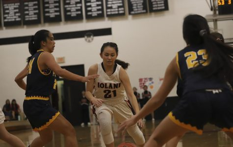 Raiders Myla Pellegrini '21 attacks the basket, finessing through the Punahou defense.